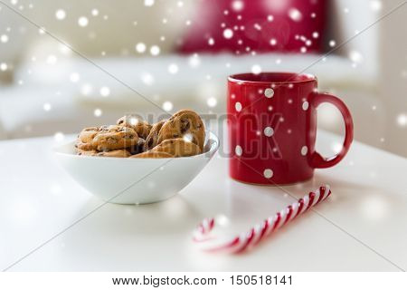 christmas, holidays, winter and celebration concept - close up of oat cookies, sugar cane candy and red cup on table at home