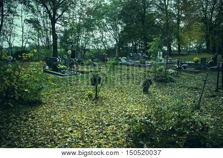 Crosses and tomb stones in autumn scene. Old graves on cemetery in Slovakia in fall. Spooky aged tombstones on grave yard with trees, leaves on the ground in All Saints' day. Hallowmas. Solemnity of All Saints