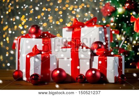 christmas, holidays, presents, new year and celebration concept - group of gift boxes and red balls under x-mas tree on wooden floor