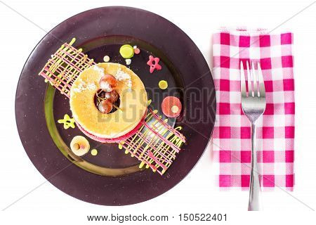 Stack of small pancakes with grape on black dish on white table