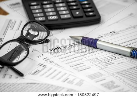 US tax form 1040 with pen glasses and calculator