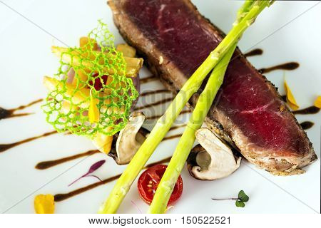 Grilled steaks on white dish in restaurant