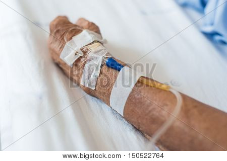 Elderly Hand With  Saline Solution On Bed