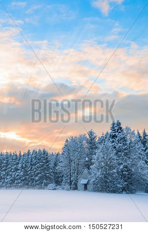 Vertical scenery of frozen forest in rural Bavarian region Allgaeu with snow-covered tiny wooden church under morning dawn sky.
