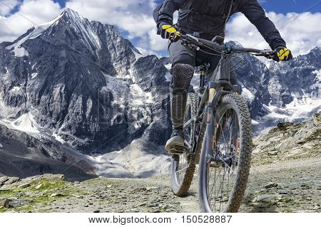 Mountain bike rider with protectors rides up a single trail in great height. The background shows the