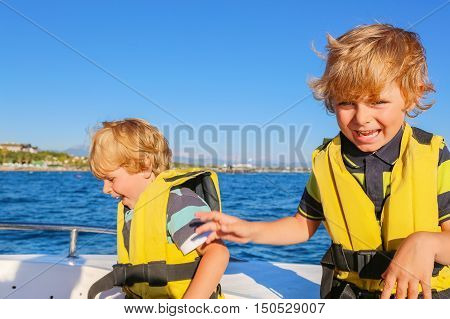 two little kid boys, best friends enjoying sailing boat trip. Family vacations on ocean or sea on sunny day. Children smiling.