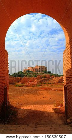 Former Saddam Hussein Palace in Babylon view through Babylonian ruins arch Iraq