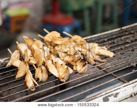 Grill Eringi mushrooms skewerd with wooden stick on the stove in the shop at the street (Selective focus) poster