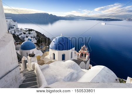 Oia town on Santorini island Greece. Traditional and famous houses and churches with blue domes over the Caldera Aegean sea