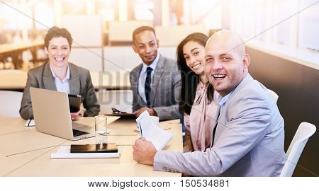 four business professionals all looking at the camera during a business meeting in a modern conference room with a large window behind them with bright natural light coming in.