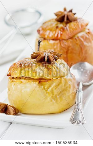 Baked apples with honey, curds, raisins and nuts in a white plate decorated ashberry on a wooden background.