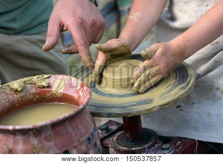 Hands working on pottery wheel in a art scool