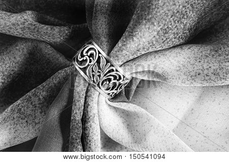 Silver carved ring on black and white draped cloth