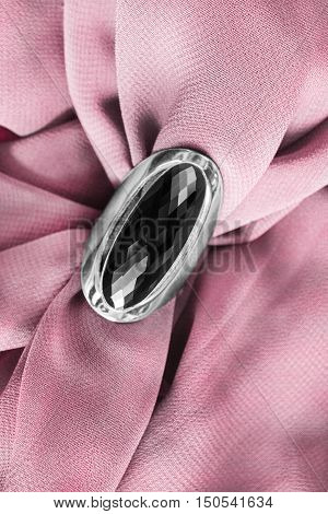 Black onyx ring on draped pink silk as a background