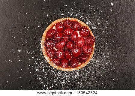 Tartlet with custard, fresh glazed aspberries and sieving sugar powder, served on vintage stone surface. Dark rustic style.