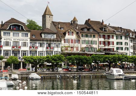 RAPPERSWIL SWITZERLAND - MAY 10 2016: Buildings hotels and moored boats along promenade by the lakeside all this shows the diversity of tourist attractions and recreational character of the city