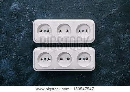 White triple electric sockets on the spotty black surface