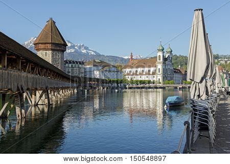 LUCERNE SWITZERLAND - MAY 05 2016: Landmarks by the river Reuss. From left can be seen roofed Chapel Bridge with octagonal stone tower and white theater building ending on Jesuit Church.