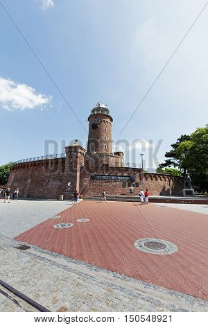 KOLOBRZEG POLAND - JUNE 22 2016: Made of red brick building of the lighthouse that is for the purposes of navigation but it is also recognizable tourist attraction