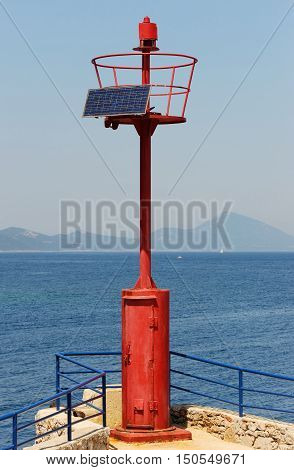 Mediterranean beacon with solar cells and coastline in the background