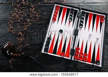 Board and pieces for the backgammon with smoking pipe and loosed tobacco. Flat lay