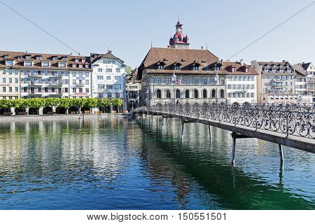 LUCERNE SWITZERLAND - MAY 05 2016: Pedestrian bridge leading to the right bank of the river Reuss where can be seen the historic architecture with massive town hall and its tower