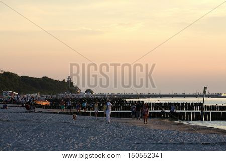 KOLOBRZEG POLAND - JUNE 24 2016: Several unidentified vacationers spend their spare time at the shoreline of the Baltic Sea at dusk and they enjoy their stroll.