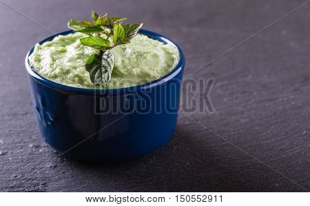 Blue Bowl With Wasabi Dip With Piece Of Herb