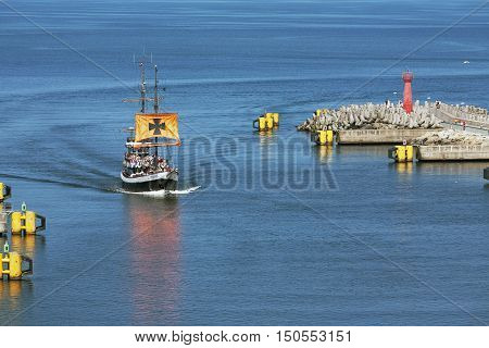 KOLOBRZEG POLAND - JUNE 22 2016: Stylized cruise ship named The Pirate enters the port the vessel returns from a trip can be seen on the waterway