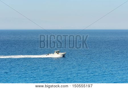 Motorboat cruising at the mediterranean sea under blue sky