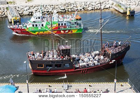 KOLOBRZEG POLAND - JUNE 22 2016: Fishing boat named Monika III enters the port and stylized cruise ship named MS Santa Maria departs from port both can be seen on the waterway