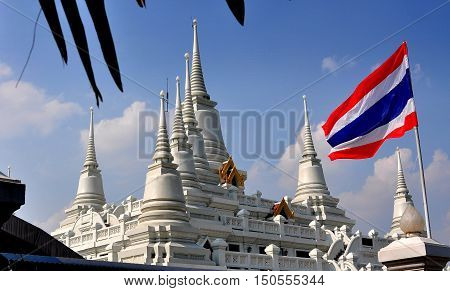 Samut Prakan Thailand - January 15 2013: Gleaming Wat Asoke and its seven chedis with ringed spires and the red white and blue Thai flag