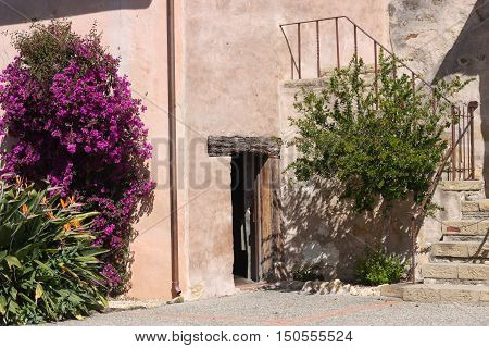 This is an image of an old door and staircase in the garden area of the Carmel Mission in Carmel, California.