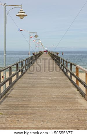 Goehren, Germany - September 22, 2016: The wooden pier at the Baltic Sea beach on a  late summer day. The structure is 350 m long and was reconstructed in 1993.