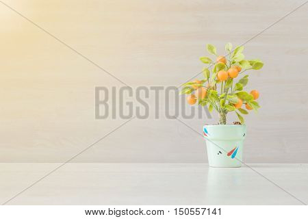Closeup artificial orange plant with orange fruit in green pot on blurred wooden desk and wall textured background in office room for decorate under window light with copy space
