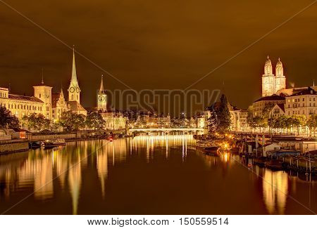 View along the Limmat river in the city of Zurich, Switzerland at night. Towers of the Fraumunster, St Peter Church and Grossmunster cathedrals. A HDR image with tone mapping applied.