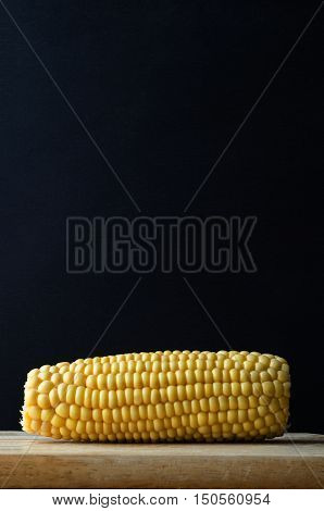 Sweetcorn Cob On Wood With Black Background