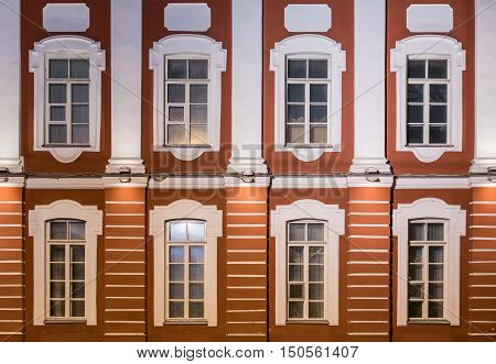 Several windows in a row on night illuminated facade of Saint Petersburg State University front view Russia poster