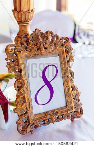 Gold frame with a number of the decorated table with the number 8.