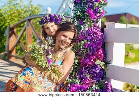 Happy mother and daughter under the arch for the wedding ceremony. Floristic composition in vintage style. The Provence.