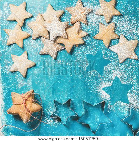 Christmas or New Year holiday food background. Sweet gingerbread cookies in shape of star sprinkled with sugar powder on blue painted plywood background, top view, copy space