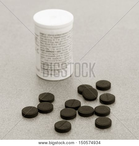 Activated Charcoal Tablets For Cleansing The Body On A Gray Background Closeup. Black And White Photo