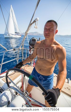 Yachtsman skipper during race, on his sailing yaht boat on the sea.