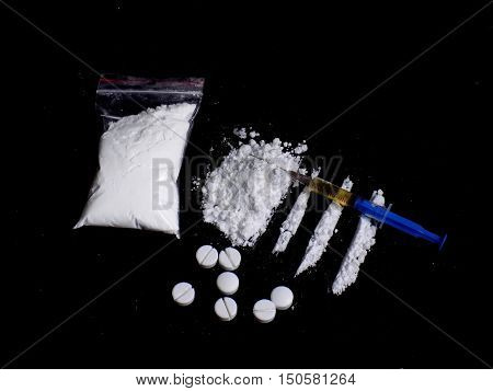 Injection syringe on cocaine drug powder pile and lines and cocaine bag and pills on black background