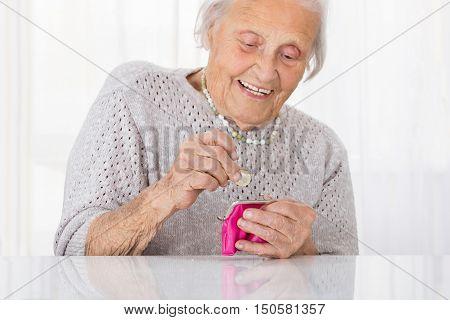 Happy Senior Woman Inserting Coin In Small Purse