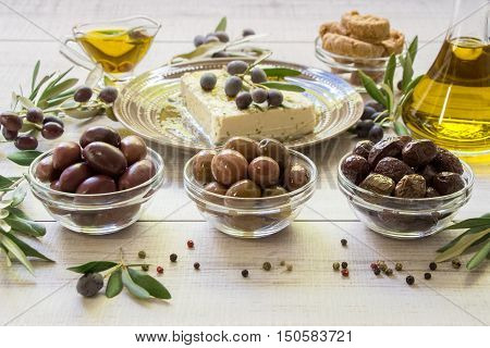 Three kinds of olives, olive oil, feta cheese, crackers framed by branches of the olive tree on a light white wooden background. Olives, olive oil, feta cheese. Horizontal. Daylight.