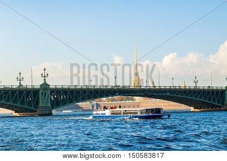 ST PETERSBURG RUSSIA-OCTOBER 3 2016. Palace Bridge and touristic pleasure boat floating under the bridge span at Neva River and Peter and Paul fortress belfry on the background in St Petersburg