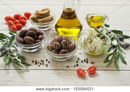 Two kinds of olives, olive oil, feta cheese, crackers, tomato cherry framed by branches of the olive tree on a light white wooden background. Olives, olive oil, feta cheese. Horizontal. Daylight.
