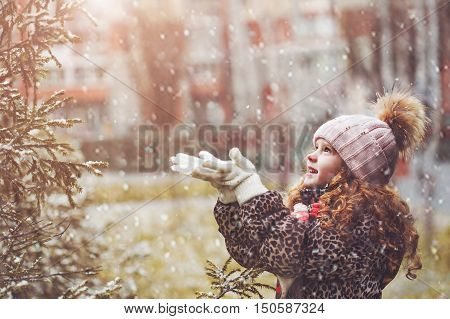 Little girl catches falling snowflakes. Child enjoy first snow in christmas holiday. Toning instagram filter.