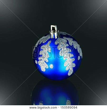 Christmas tree ornament - blue glass ball with Christmas ornament on a black background. the photo has a empty space for your text